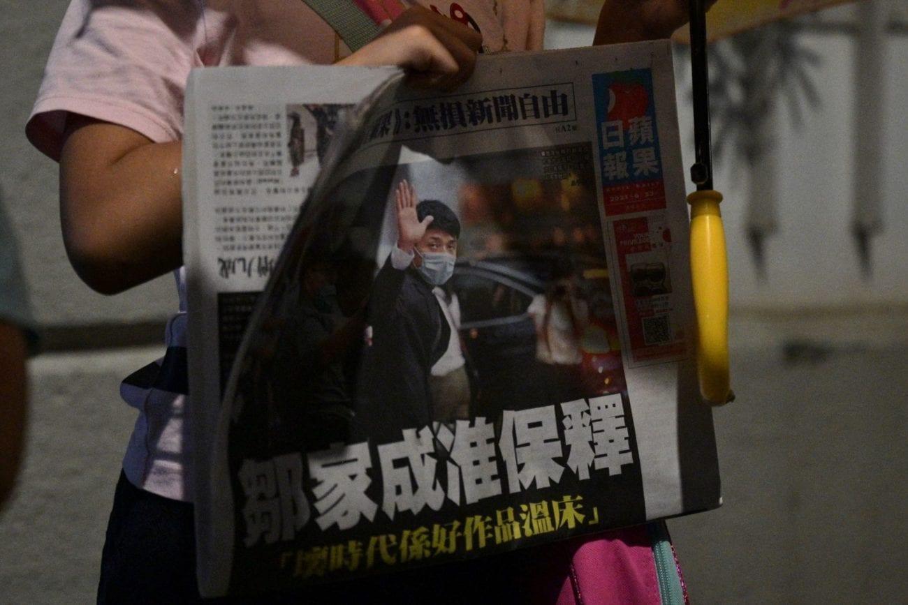 Un enfant tient l'édition du 23 juin 2021 du journal hongkongais Apple Daily. [Anthony Wallace - AFP]