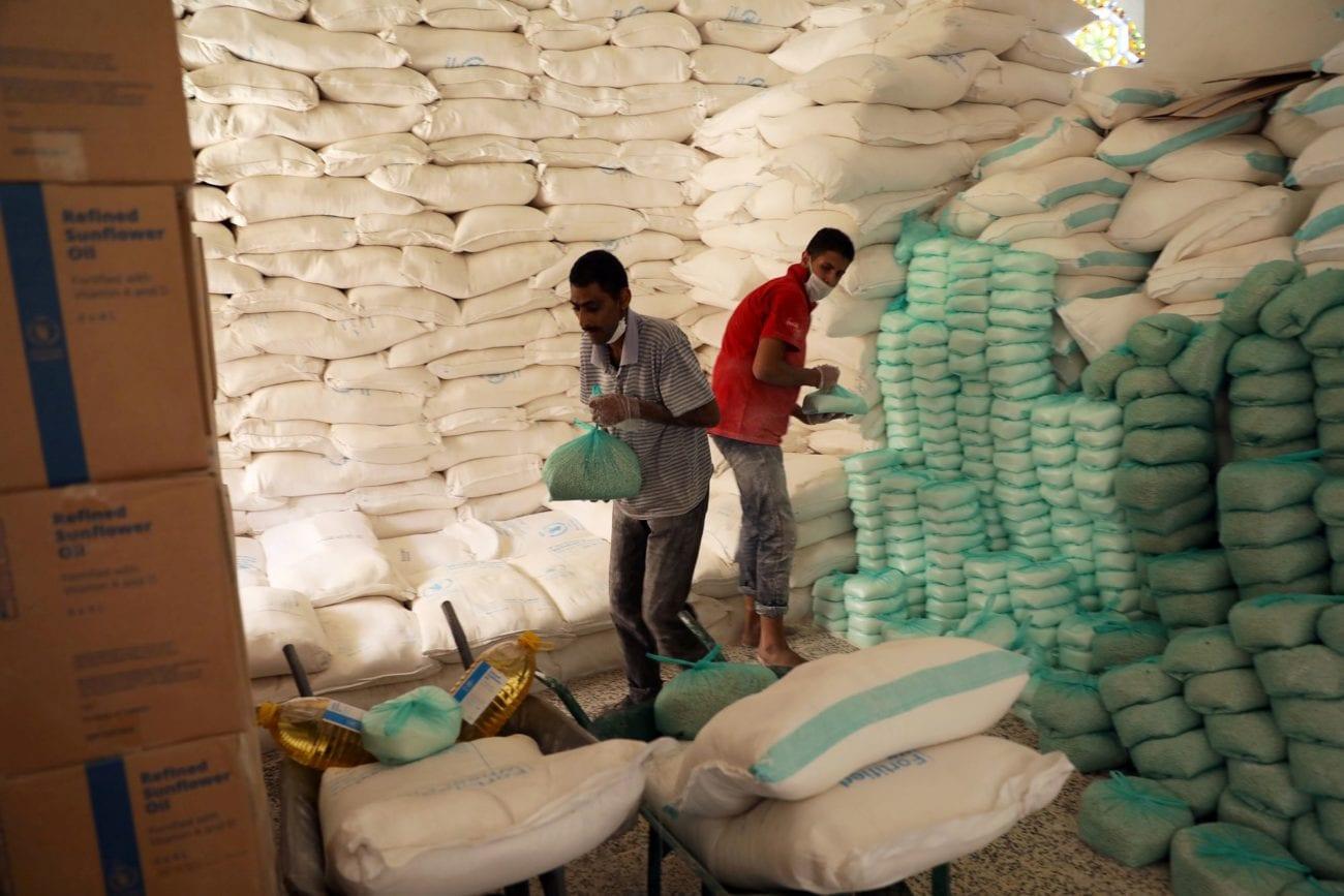 Des travaillers préparent des stocks de nourriture à distribuer à Sanaa