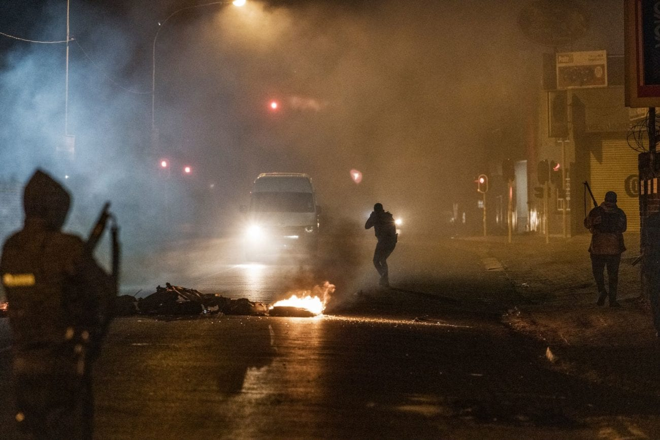 Des forces de police sud-africaines tentent d'arrêter l'avancée d'un minivan dans un contexte d'émeutes