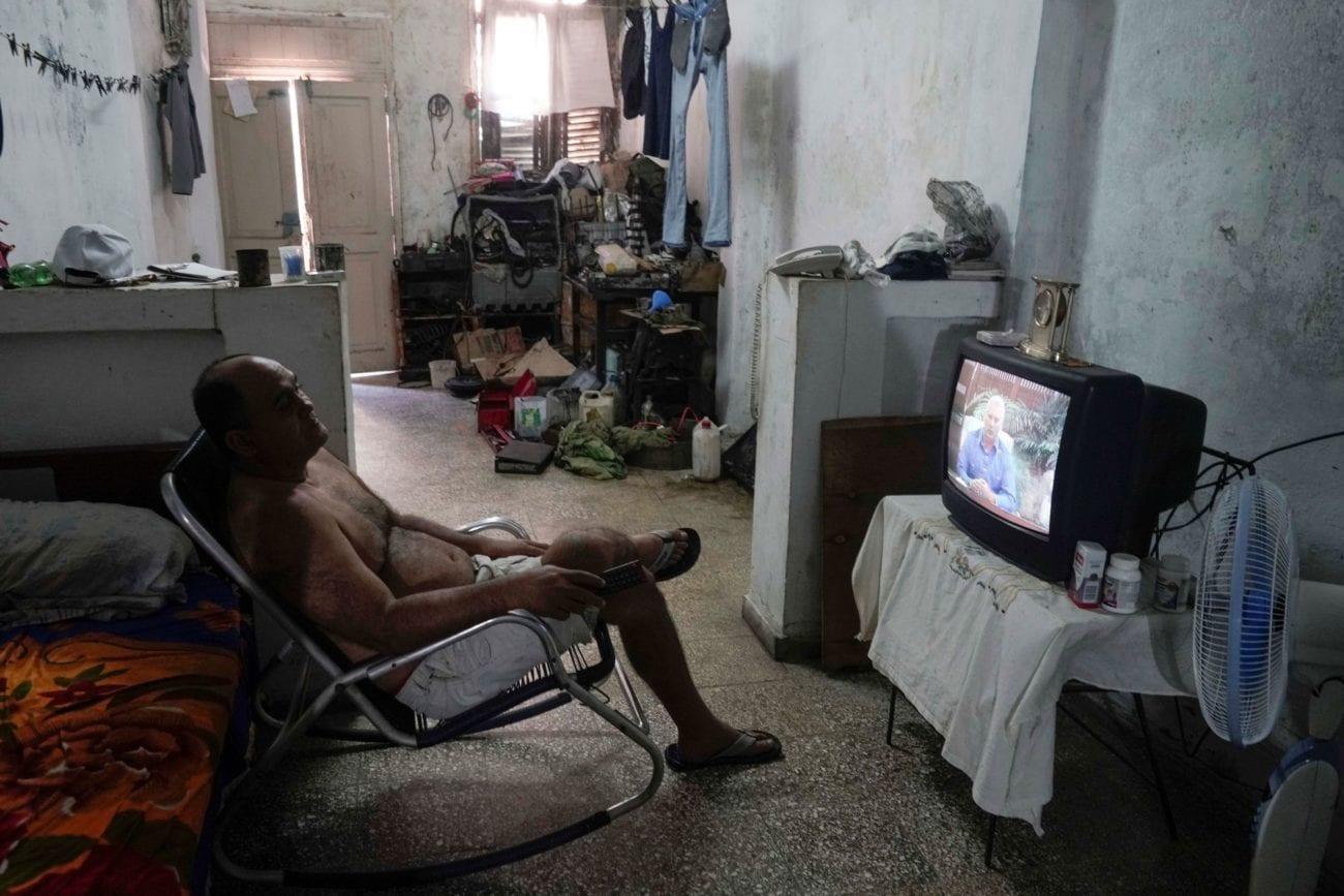 Un vendeur de rue regarde un discours du président cubain