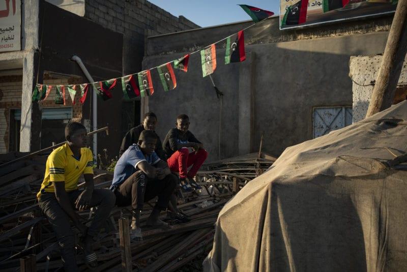 De jeunes migrants attendent d'être engagé à la journée à un carrefour des faubourgs de Tripoli