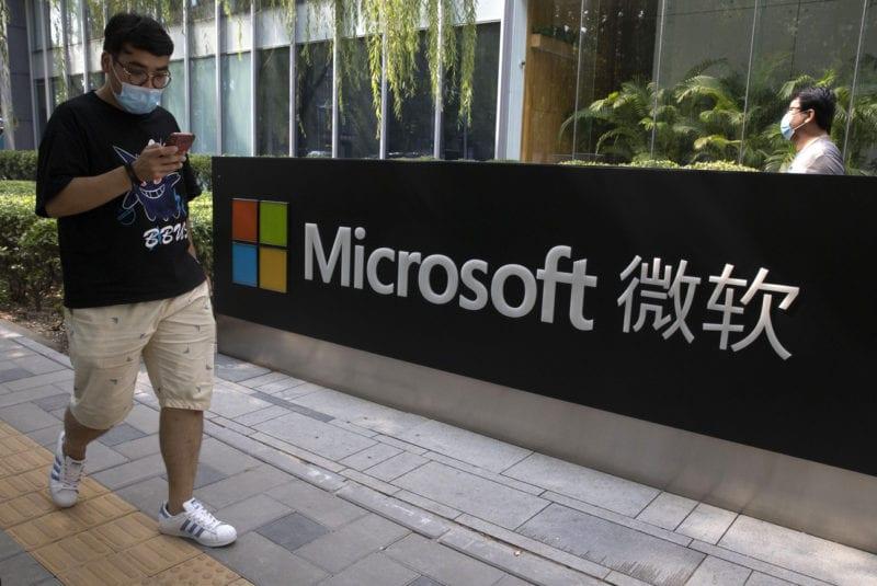 Un homme regarde son téléphone devant le siège de Microsoft à Pékin. [Ng Han Guan / AP Photo - KEYSTONE]