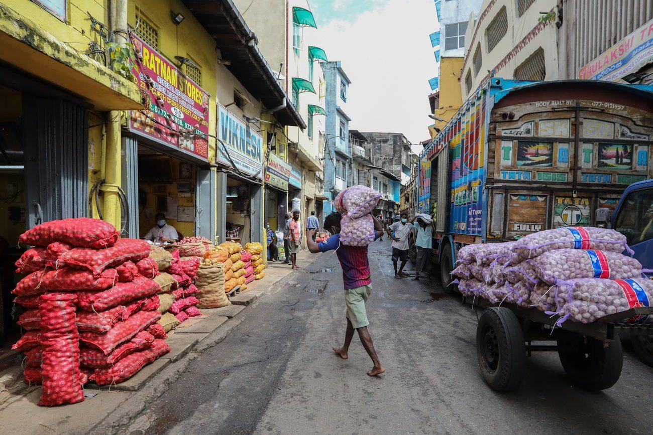 Des travailleurs déchargent des produits alimentaires essentiels sur un marché de gros à Colombo