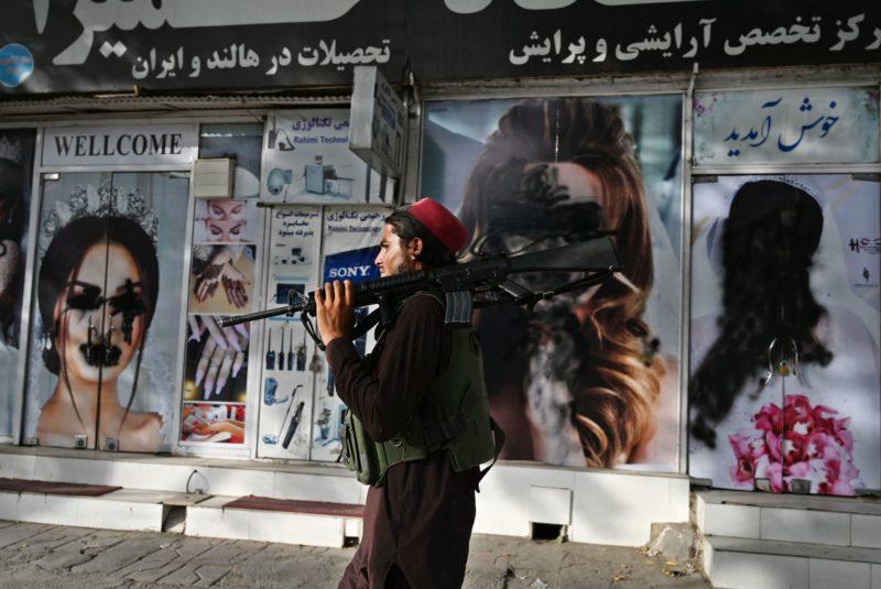 Un combattant taliban passe devant un salon de beauté avec des images de femmes recouvertes de peinture